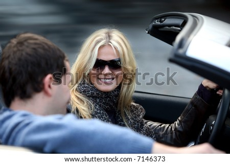 Blond woman and a man in a convertible car - stock photo