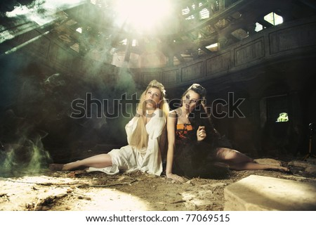 Blond woman and beauty brunette in abandon building - stock photo