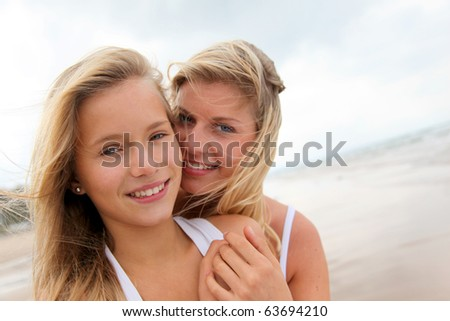 Blond woman and young girl on a sandy beach - stock photo