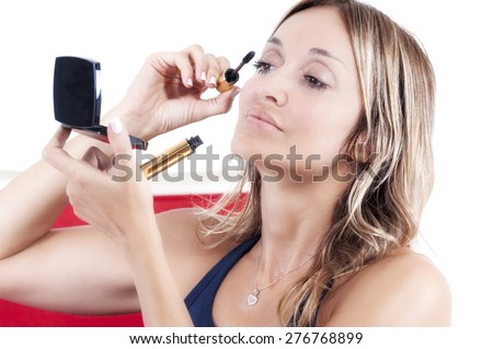 blond woman applying eye shadow to her eyes