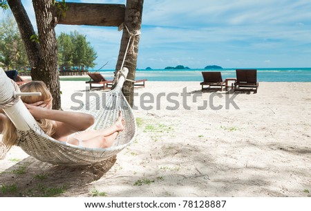Blond woman asleep in a hammock. - stock photo