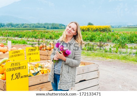Blond woman at autumn countryside farm market holding bright flowers, pumpkin on background - stock photo
