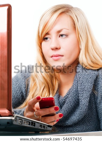 blond woman calling by phone and working on laptop