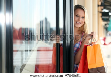 Blond woman coming out of clothes shop - stock photo