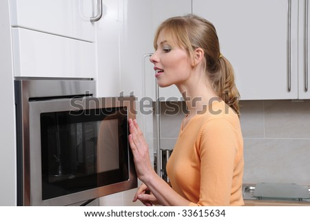 Blond woman cooking with a microwave in a modern kitchen - stock photo