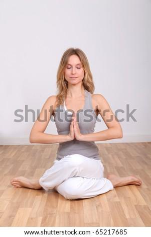 Blond woman doing yoga exercises - stock photo