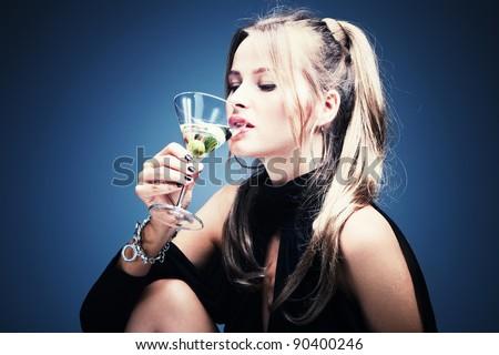 blond woman drinking martini, studio shot - stock photo