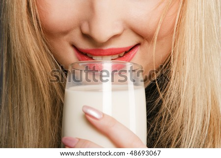 Blond woman drinking milk from glass close-up portrait - stock photo