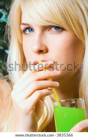 blond woman drinks kiwi juice from the glass and straw