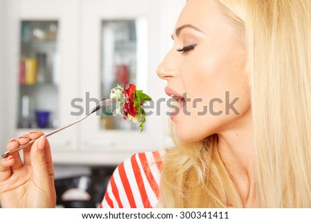 blond woman eating a salad in her kitchen