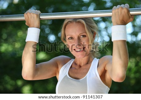 Blond woman exercising on pull-up bar outdoors - stock photo