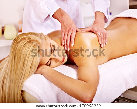 Blond woman getting massage in health resort. - stock photo