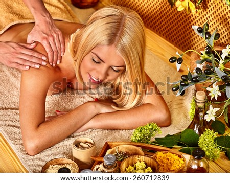 Blond woman getting massage in tropical spa. - stock photo