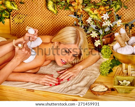 Blond woman getting massage in tropical spa. Bamboo background. - stock photo