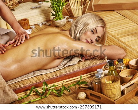 Blond woman getting massage in tropical spa.Bamboo floor. - stock photo
