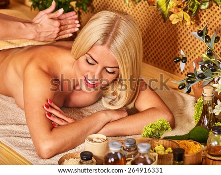 Blond woman getting massage in tropical spa. Eyes closed.