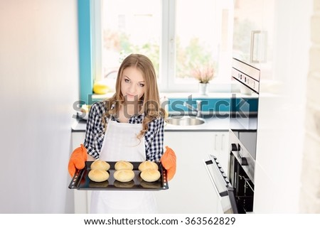 Blond woman holding a baking tray with freshly baked bread rolls. Orange kitchen gloves on hands - stock photo