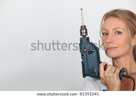 Blond woman holding electric drill