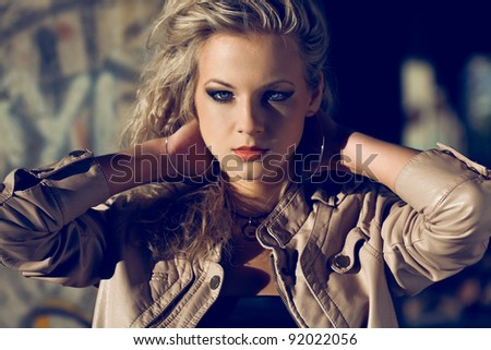 blond woman holding hands at the back wearing leather jacket inside ruins. Fashion photo - stock photo