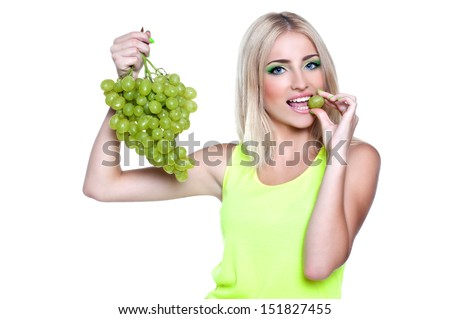 blond woman holding ripe grapes, on white - stock photo