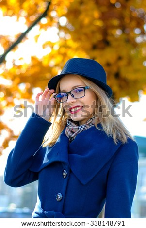 Blond woman in a blue hat straightens glasses and smiling on a background of yellow foliage