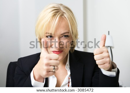 blond woman in a suit showing thumbs-up