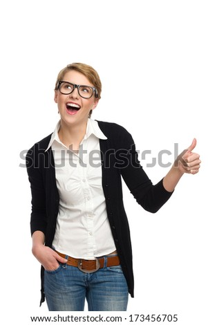 Blond woman in green glasses shoeing thumb up. Three quarter length studio shot isolated on white. - stock photo