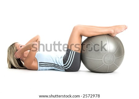 Blond woman in gym outfit excercising with a pilates ball - stock photo