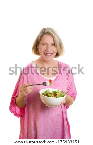 Blond woman in her 50s eating salat out of a bowl, copy space, isolated