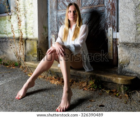 Blond woman in hot pants sitting in front of an weathered door