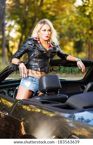 Blond woman in leather jacket and jeans shorts in convertible car.