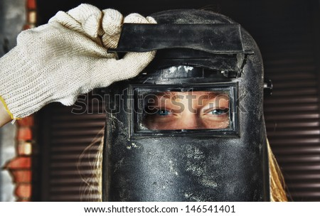 blond woman in overall and welder helmet - stock photo