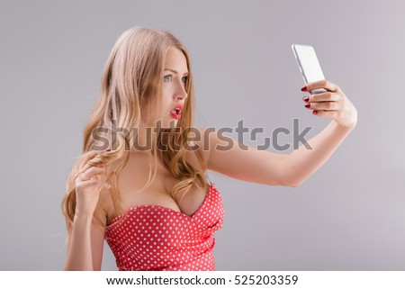 blond woman in red dress makes selfie on phone