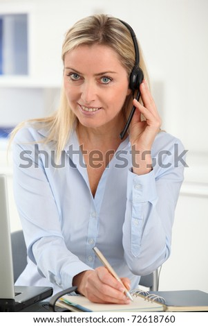 Blond woman in the office with headset on