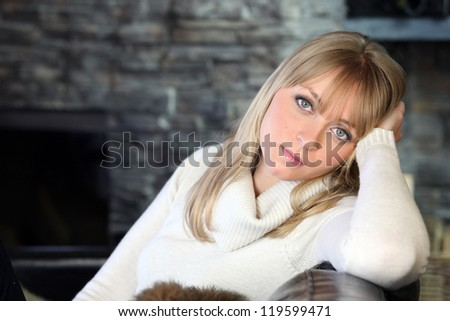 Blond woman in turtle neck jumper sat on coach