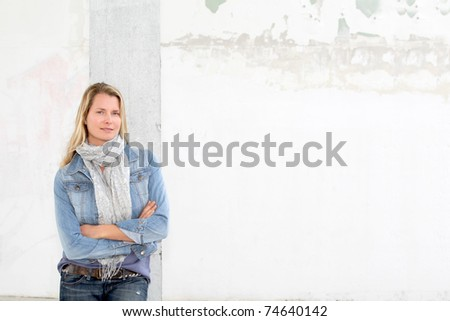 Blond woman leaning on concrete wall - stock photo