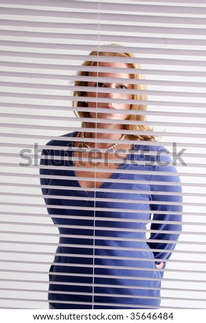 Blond woman looking through blinds