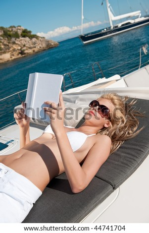 Blond woman lying on yacht reading book sunbathing on sunny day - stock photo