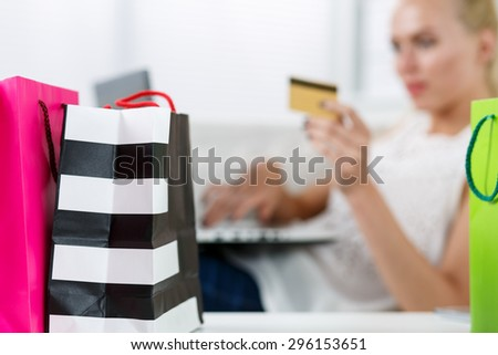 Blond woman making purchasing via internet paying credit card. Focus on fresh buying packed in colored paper bags standing in front of her. Shopping, consumerism, delivery and present concept - stock photo