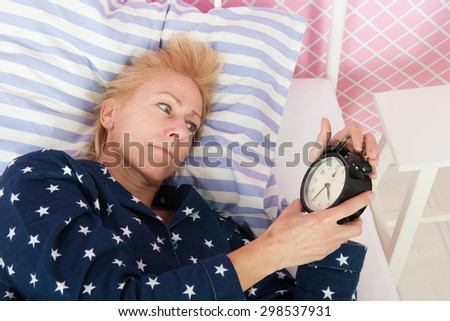 Blond woman of mature age with insomnia - stock photo