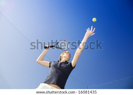 blond woman playing tennis, about to hit the ball. Copy space - stock photo