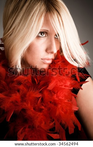 blond woman portrait with red plumage - stock photo
