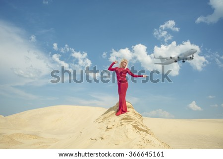 blond woman posing in red dress with a long dress stand on sand desert against sky with clouds and airplane. young adult girl dancing.  - stock photo