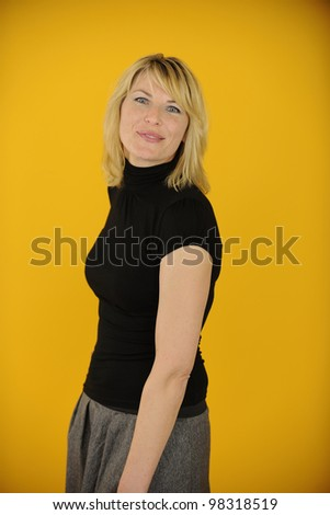 blond woman posing on yellow background - stock photo
