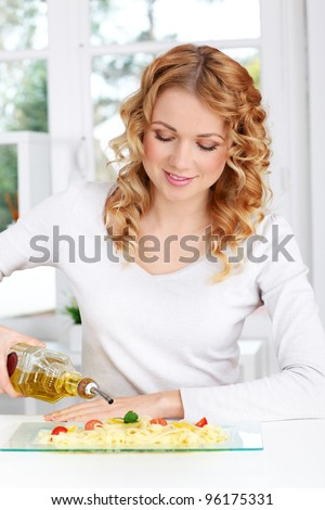 Blond woman pouring olive oil on pasta dish