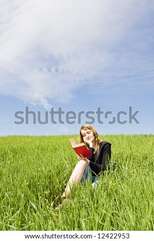 Blond woman reading over the grass - stock photo
