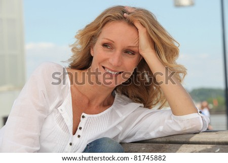 Blond woman relaxing on park bench - stock photo