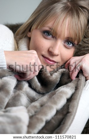 Blond woman relaxing under blanket
