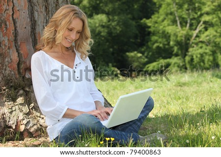 Blond woman sat by tree with laptop computer - stock photo