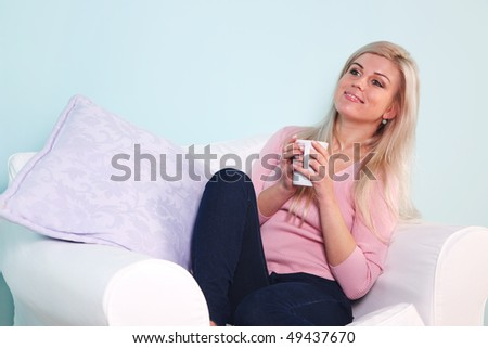 Blond woman sat in an armchair holding a white mug looking and smiling out of frame.